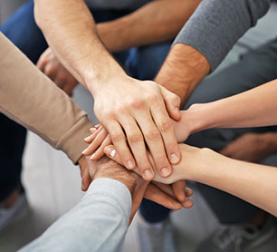 People putting hands together during group therapy. Men's healthy relationships group in Los Angeles, CA.