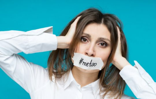 woman holding her head, with a tape on her mouth with a #metoo text