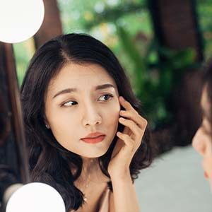 Asian girl looking at the mirror.