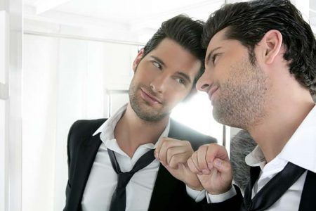 Handsome narcissistic man looking at the mirror.