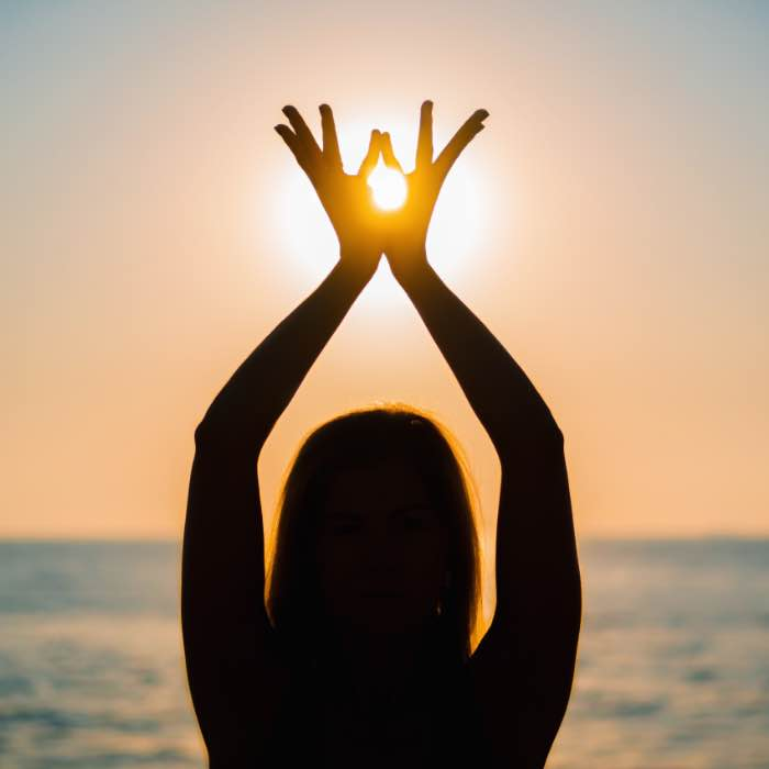 Silhouette of female hands on sun background.