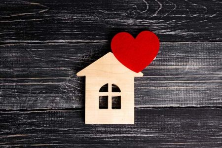 Wooden house with red heart illustration.