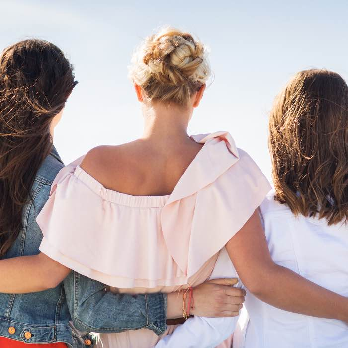 Group of young women in casual clothes hugging.
